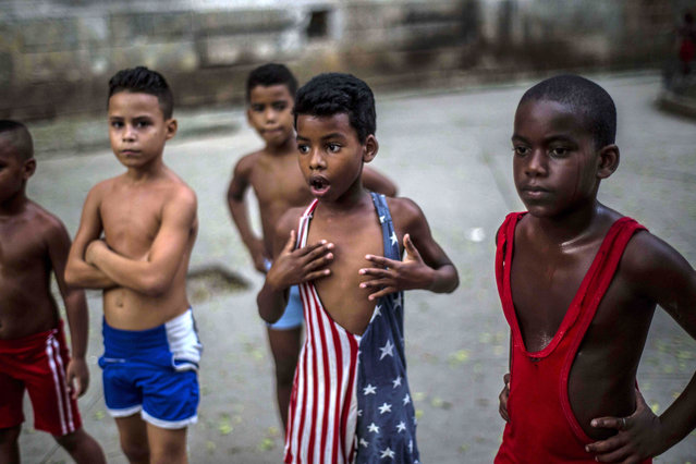 In his October 15, 2014 file photo, 8-year-old Yodimiler Arias, along with fellow wrestlers, listen to instruction from their teacher, in a park in Old Havana, Cuba. Yodimiler's mother said the U.S. flag motif wrestling suit was sent by her cousin in the United States. (Photo by Ramon Espinosa/AP Photo)