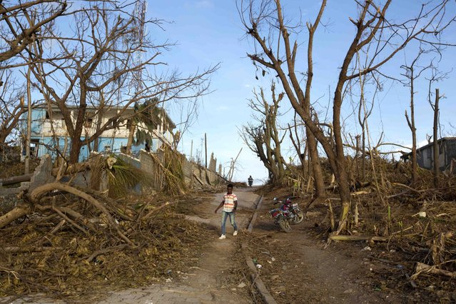 A man walks past the debris left by Hurricane Matthew in Dame-Marie, Haiti on Monday, October 10, 2016. Nearly a week after the storm smashed into southwestern Haiti, some communities along the southern coast have yet to receive any assistance, leaving residents who have lost their homes and virtually all of their belongings struggling to find shelter and potable water. (Photo by Dieu Nalio Chery/AP Photo)