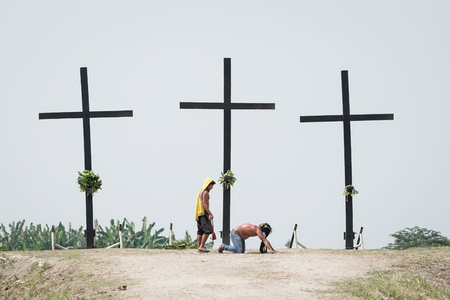 A flagellant is whipped on his back at a crucifixion site on Good Friday in San Pedro village, San Fernando, Pampanga, Philippines, 30 March 2018. Thousands of Catholic devotees witnessed dozens of men who were nailed to wooden crosses or flogged themselves bloody in annual rituals re-enacting the crucifixion of Jesus Christ. (Photo by Mark R. Cristino/EPA/EFE)