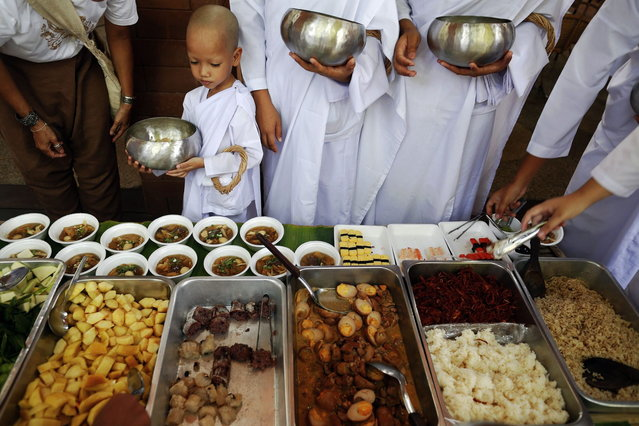A girl joins other novice nuns for a lunch at the Sathira-Dhammasathan Buddhist meditation centre in Bangkok April 21, 2013. A group of Thai girls are choosing to spend part of their school holidays as Buddhist nuns, down to having their heads shaven at the meditation centre. The centre, founded in 1987, is a learning community for peace and harmony that has programs open to people regardless of age and gender. (Photo by Damir Sagolj/Reuters)