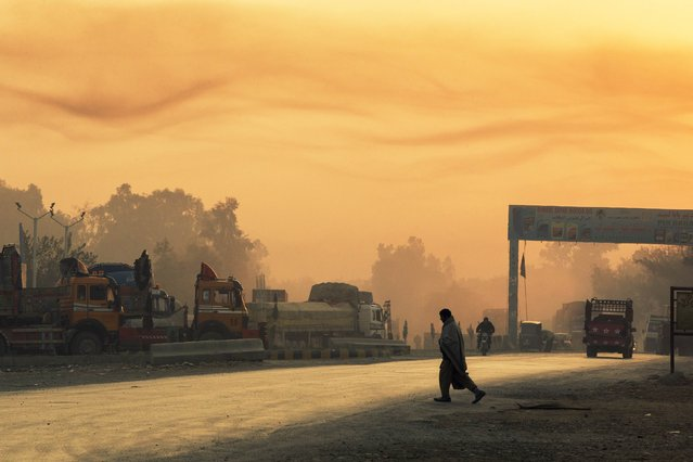 The rising sun lights smoke in the air as a man crosses the street near Forward Operating Base Fenty in the Nangarhar province of Afghanistan December 19, 2014. (Photo by Lucas Jackson/Reuters)