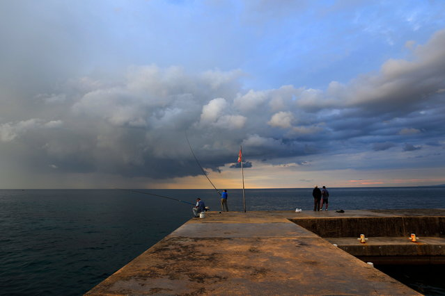 Lebanese fishermen stand on a breakwater along the Beirut coastline as they fish while the sun sets over the Mediterranean Sea in Beirut, Lebanon, Thursday, October 29, 2015. (Photo by Hassan Ammar/AP Photo)