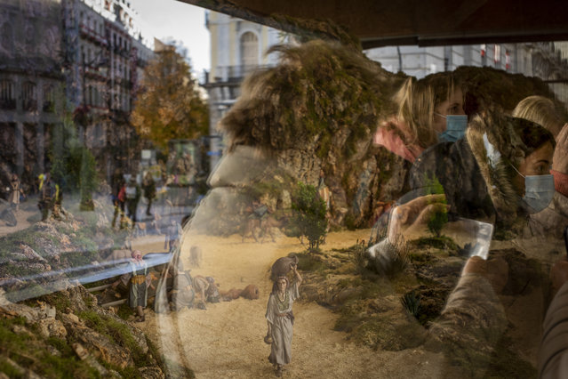 People watch a Christmas nativity scene in downtown Madrid, Spain, Thursday, December 3, 2020. Spain will slightly ease the country's curfew restrictions on some days over the Christmas holidays while keeping most limits in place due to the pandemic. (Photo by Bernat Armangue/AP Photo)