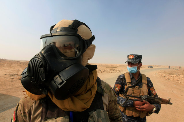 Iraqi forces wear protective masks after winds brought fumes from a nearby sulfur plant set alight by Islamic State militants, at south of Mosul in Qayyara, Iraq, October 22, 2016. (Photo by Alaa Al-Marjani/Reuters)