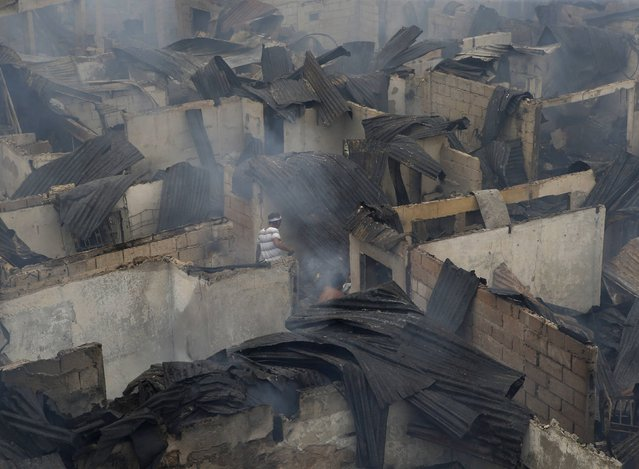 Fire victims sift through the ruins of their homes gutted by a fire at a slum colony in Quezon city, Metro Manila January 1, 2015. (Photo by Erik De Castro/Reuters)