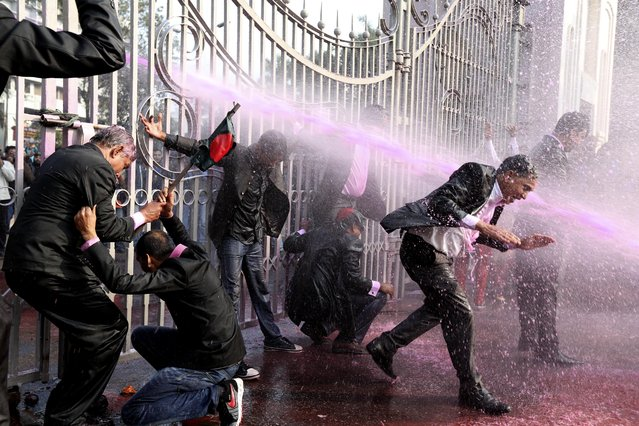 Bangladesh Natinonalist Party (BNP) supported lawyers are hit by a police water cannon in front of the main gate of the Supreme Court during the March For Democracy protest rally in Dhaka, Bangladesh, December 29, 2013.  (Photo by Abir Abdullah/EPA)