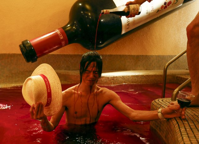 A man pours wine over the head of a customer as he stands in a hot bath with coloured water representing wine at the Hakone Kowaki-en Yunessun spa resort during an event marking Beaujolais Nouveau Day in Hakone west of Tokyo, November 19, 2015. (Photo by Thomas Peter/Reuters)