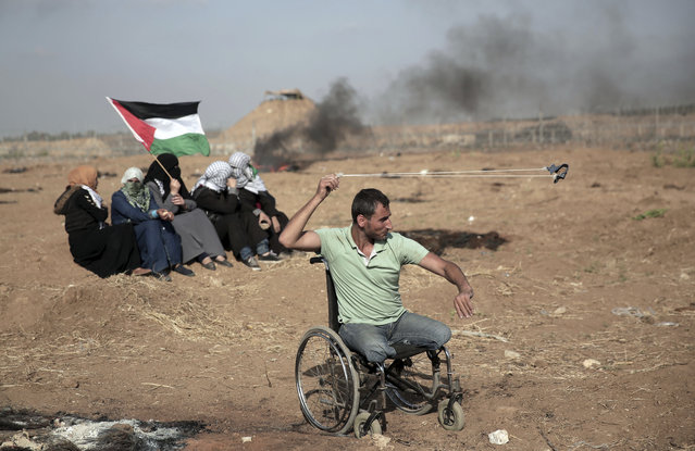 A disabled Palestinian protester hurls stones at Israeli troops during a protest at the Gaza Strip's border with Israel, Friday, May 11, 2018. Gaza activists burned tires near the sealed border with Israel on Friday in a seventh weekly protest aimed at shaking off a decade-old blockade of their territory. Israeli soldiers fired tear gas volleys from the other side of the border fence. (Photo by Khalil Hamra/AP Photo)