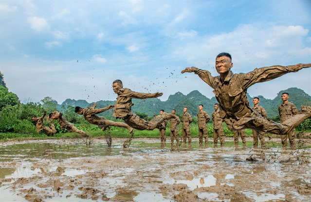 The officers and soldiers of the armed police carry out reverse training in the mire. Chongzuo, Guangxi, China, May 6, 2020. (Photo by Costfoto/Barcroft Media via Getty Images)