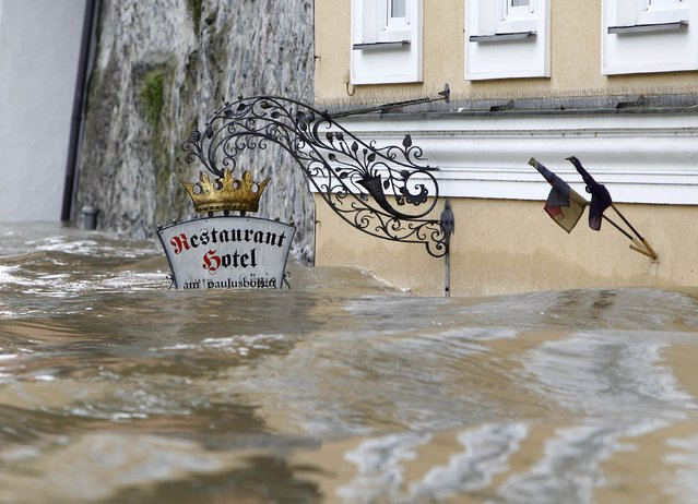 The sign above the door of restaurant and hotel 'Am Paulusbogen' is partially submerged in the flooded centre of the Bavarian town of Passau, about 200 km (124 miles) north-east of Munich June 3, 2013. Torrential rain in the south and south-east of Germany caused heavy flooding over the weekend, forcing people to evacuate their homes. (Photo by Michaela Rehle/Reuters)