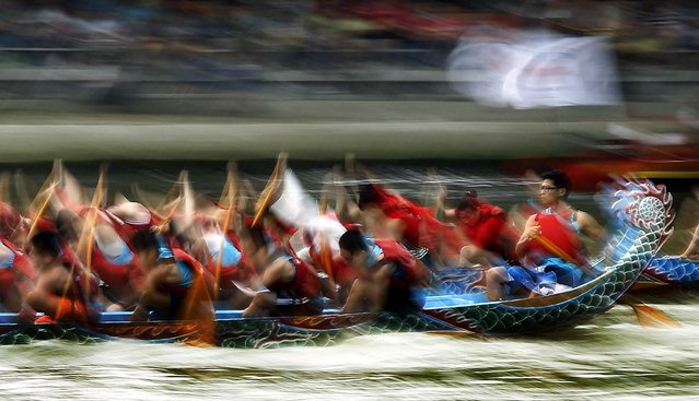A helmsman steadily steers his boat during the annual Dragon Boat Festival races in Taipei, Taiwan. Dragon boat races are held in remembrance of Chu Yuan, an ancient Chinese scholar-statesman, who drowned in 277 B.C. while denouncing government corruption. (Photo by Wally Santana/Associated Press)