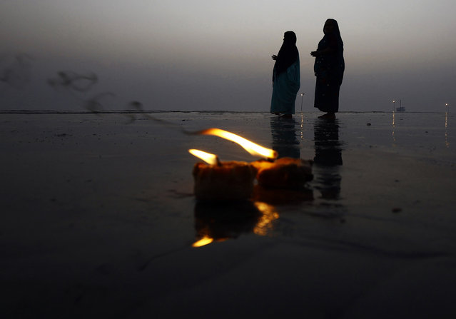 "Hindu pilgrims pray behind burning oil lamps after they took a holy dip at the confluence of the river Ganges and the Bay of Bengal, ahead of the ""Makar Sankranti"" festival at Sagar Island, south of Kolkata, January 12, 2015. (Photo by Rupak De Chowdhuri/Reuters)"