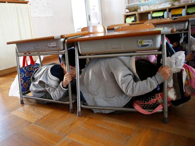 School children take shelter under desks during a tsunami simulation drill ahead of World Tsunami Awareness Day at Futaba elementary school in Choshi, Chiba Prefecture, Japan, November 4, 2016. (Photo by Kim Kyung-Hoon/Reuters)