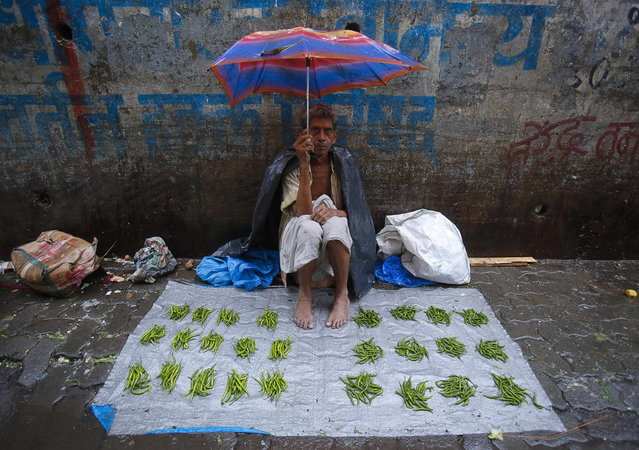 A vegetable vendor sits under an umbrella on a tarpaulin sheet at a market during monsoon rains in Mumbai June 18, 2013. The rains are at least twice as heavy as usual in northwest and central India as the June-September monsoon spreads north, covering the whole country a month faster than normal. (Photo by Vivek Prakash/Reuters)