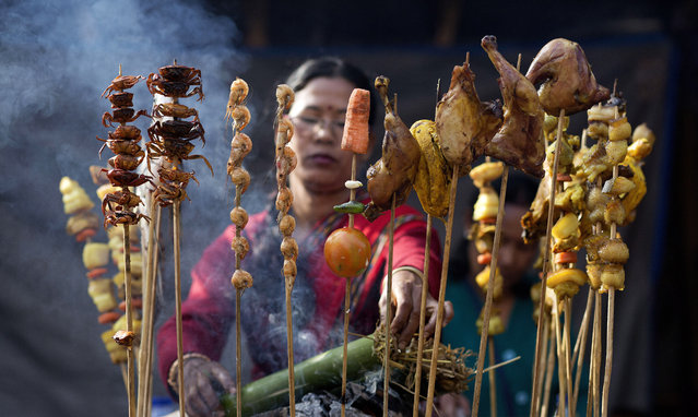 A Mishing tribal woman smokes meat at a temporary stall during an ongoing ethnic food festival as part of festivities to mark Bhogali Bihu festival in Gauhati, India , Saturday, January 10, 2015. Bhogali Bihu is the harvest festival of Assam state and is observed in January every year. (Photo by Anupam Nath/AP Photo)