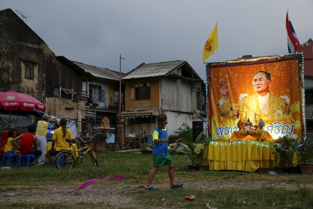 A boy runs next to a portrait of Thailand's King Bhumibol Adulyadej, placed in celebration of the King's 88th birthday, in Bangkok, Thailand, December 5, 2015. (Photo by Jorge Silva/Reuters)