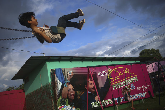 In this Friday, November 4, 2016 photo, a boy swings in a park next to an election billboard promoting Nicaragua's President Daniel Ortega and running mate, his wife Rosario Murillo, in Managua, Nicaragua. Ortega appears to have a clear path to a third consecutive term following recent moves that weakened the country's opposition. Polls show the former guerrilla fighter easily winning with more than 50 percent of the vote. (Photo by Esteban Felix/AP Photo)