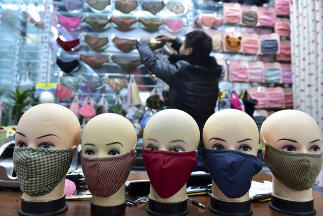 A vendor arranges a shelf full of masks as he waits for customers in a shopping mall in Yiwu, Zhejiang province, China, December 7, 2015. Picture taken December 7, 2015. (Photo by Reuters/China Daily)