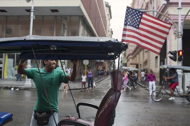 Bici taxi driver Yosvani Gomes, 39, lifts the curtains of his vehicle after a rain in downtown Havana January 20, 2015. (Photo by Alexandre Meneghini/Reuters)