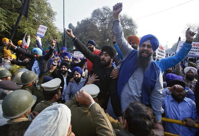 """Indian policemen (L) try to stop demonstrators from the Sikh community from crossing over the barricades during a protest against the impending release of an Indian film """"MSG: The Messenger of God"""", in New Delhi January 16, 2015. Several groups representing the Sikh minority. (Photo by Anindito Mukherjee/Reuters)"""