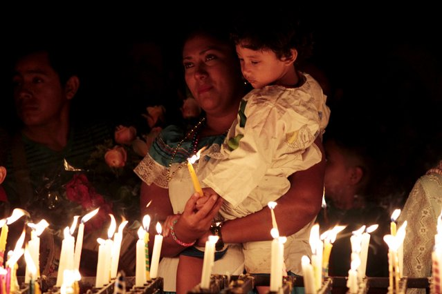 Devotees light candles to celebrate the Day of the Virgin of Guadalupe outside the Basilica of Guadalupe in San Salvador, El Salvador December 12, 2015. (Photo by Jose Cabezas/Reuters)