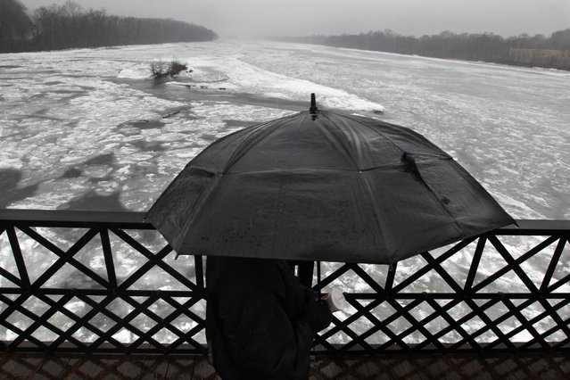 A man uses an umbrella as he walks in the rain on the Calhoun Street Bridge over an ice-clogged Delaware River, Sunday, January 18, 2015, in Trenton, N.J. (Photo by Mel Evans/AP Photo)