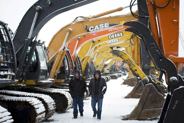 Buyers look over machinery at the Ritchie Brothers Auction in Nisku, Alberta on December 11, 2015. The world's largest industrial auctioneer stresses it sells more than oilfield equipment, but it is no secret that many sellers are oil companies reeling from the 18-month rout that has driven crude prices near 11-year lows this week. (Photo by Topher Seguin/Reuters)