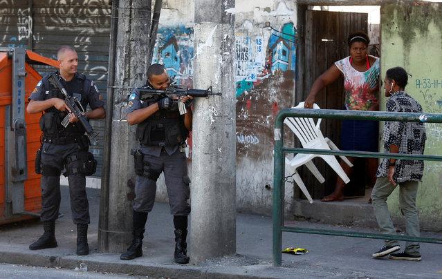 Policemen take position during an operation against drug dealers in Cidade de Deus or City of God slum in Rio de Janeiro, Brazil, November 20, 2016. (Photo by Ricardo Moraes/Reuters)