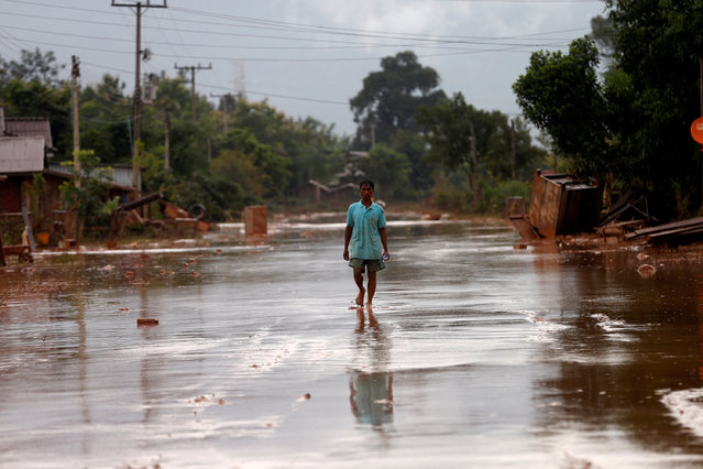 A man walks on a street during the flood after the Xepian-Xe Nam Noy hydropower dam collapsed in Attapeu province, Laos July 26, 2018. (Photo by Soe Zeya Tun/Reuters)