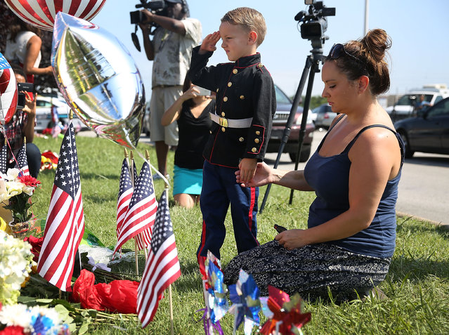 Blake Miller and his mother, Ashley Miller whose husband is a Lieutenant in the Marine Corps pay their respects to those killed while visiting a memorial placed in front of the Armed Forces Career Center/National Guard Recruitment Office which had been shot up on July 17, 2015 in Chattanooga, Tennessee. (Photo by Joe Raedle/Getty Images)