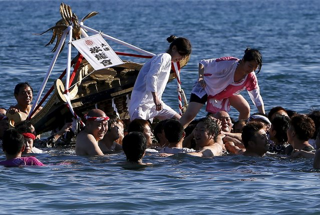"Women balance on a ""mikoshi"" or portable shrine as people carry it into the sea during a festival to wish for calm waters in the ocean and good fortune in the new year in Oiso, Kanagawa prefecture, west of Tokyo, Japan, January 1, 2016. (Photo by Yuya Shino/Reuters)"