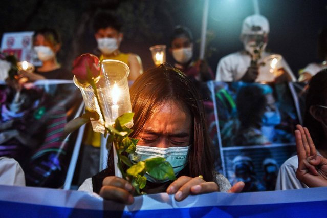 A Myanmar migrant living in Thailand cries during a memorial in Bangkok on March 4, 2021 to honour those who died during demonstrations against the military coup in their homeland. (Photo by Lillian Suwanrumpha/AFP Photo)