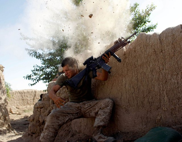 Sgt. William Olas Bee, a U.S. Marine from the 24th Marine Expeditionary Unit, has a close call after Taliban fighters opened fire near Garmser in Helmand Province of Afghanistan May in this 18, 2008 file photo. (Photo by Goran Tomasevic/Reuters)