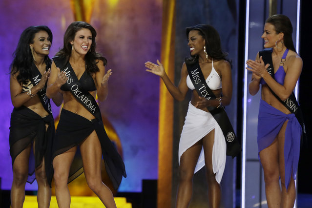 Miss Oklahoma Kelsey Griswold, center, reacts after finding out she's advancing beyond the lifestyle competition as Miss New York Nina Davuluri, from left, Miss Texas Ivana Hall, and Miss Wisconsin Paula Mae Kuiper look on during the Miss America 2014 pageant, Sunday, September 15, 2013, in Atlantic City, N.J. (Photo by Mel Evans/AP Photo)