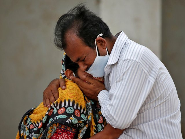 A woman is consoled by her relative after her husband died from the coronavirus disease (COVID-19) outside a COVID-19 hospital in Ahmedabad, India, April 26, 2021. (Photo by Amit Dave/Reuters)