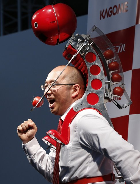"Kagome Co's employee Shigenori Suzuki poses with the newly-developed ""Wearable Tomato"" device for runners during its unveiling event ahead of the weekend's Tokyo Marathon in Tokyo February 19, 2015. (Photo by Toru Hanai/Reuters)"