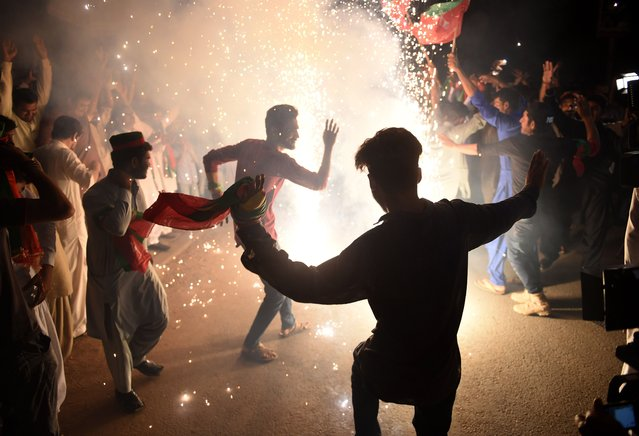 """Supporters of Pakistan's cricketer-turned politician Imran Khan, and head of the Pakistan Tehreek-e-Insaf (Movement for Justice) party, celebrate in Karachi on July 26, 2018, a day after a general election. Pakistan cricket hero turned politician Imran Khan has claimed victory on July 26, in the country's tense general election marred by allegations of """"blatant"""" rigging by rival parties. A visibly tired Khan cut a conciliatory tone in a wide-ranging address to the nation following a controversial contest hit by accusations from major political parties of poll rigging and long delays in still unreleased official results. (Photo by Rizwan Tabassum/AFP Photo)"""