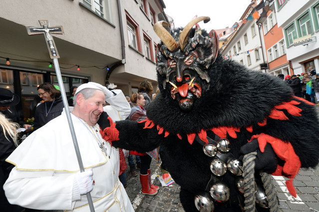 An Alttann devil rides past carnival visitor Thomas Rapp, dressed as the Pope, during the Rosenmontag (Shrove Monday) parade, a traditional carnival celebration, in the historic old town of Ravensburg,Germany, 16 February 2015. The Rose Monday parades are the highlight of the German carnival. (Photo by Felix Kaestle/EPA)