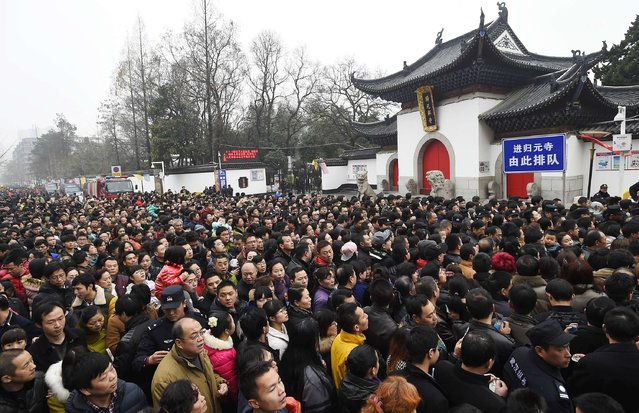 People wait to enter the Guiyuan Buddhist temple to worship the god of fortune on the fifth day of the Chinese Lunar New Year in Wuhan, Hubei province, February 23, 2015. (Photo by Reuters/Stringer)