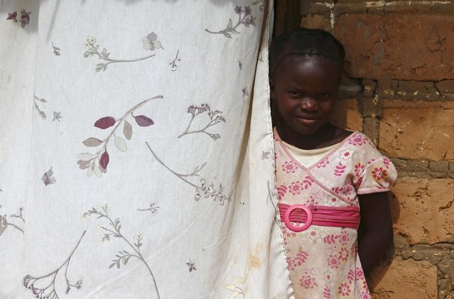 A child looks out from behind a curtain during a visit by a home-based care team to an HIV-positive person in the village of Choongo, south of the Chikuni Mission in the south of Zambia February 23, 2015. (Photo by Darrin Zammit Lupi/Reuters)