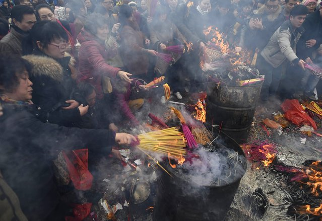 People burn incense to worship the god of fortune on the fifth day of the Chinese Lunar New Year at Guiyuan Buddhist temple in Wuhan, Hubei province, February 23, 2015. (Photo by Reuters/Stringer)