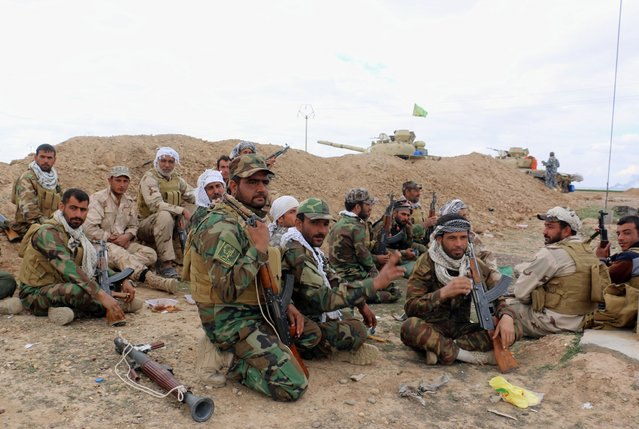 In this Wednesday, March 4, 2015 photo, Shiite militiamen rest behind a sand berm as the Iraqi army, supported by volunteers, battles Islamic State extremists outside Tikrit, 80 miles (130 kilometers) north of Baghdad, Iraq. Iranian-backed Shiite militias and Sunni tribes have joined Iraq's military in a major operation to retake Tikrit from the Islamic State group, while the U.S. led coalition has remained on the sidelines. (AP Photo)