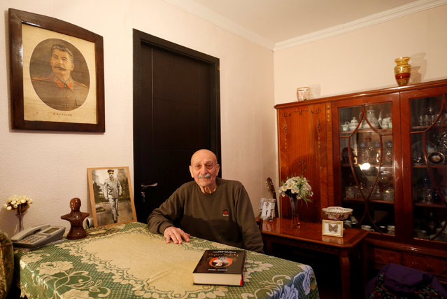 """Retired railway worker Suliko Berdzenishvili, 82, poses for a portrait at his home in Tbilisi, Georgia, November 25, 2016. """"I am a fan of his since childhood. I own portraits and books about Stalin. Most of them I bought myself, some I got as gifts"""", said Berdzenishvili. """"I go to Stalin's hometown of Gori every year to mark his birthday"""". (Photo by David Mdzinarishvili/Reuters)"""