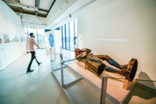 """A view of the statue of slave trader Edward Colston, which was toppled during a protest on June 7, 2020 on display at the M Shed as part of the preview of """"The Colston statue: What next?"""", in Bristol, England, Thursday June 3, 2021. A statue of a 17th-century slave trader that was toppled during anti-racism protests in the English city of Bristol is being displayed in a museum, with visitors being asked to help decide its fate. The bronze likeness of Edward Colston was pulled from its pedestal and dumped in Bristol harbor a year ago, sparking a nationwide debate about commemoration and Britain's slave-trading history. City workers hauled the statue out of the water and have kept it in storage ever since. (Photo by Ben Birchall/PA Wire via AP Photo)"""