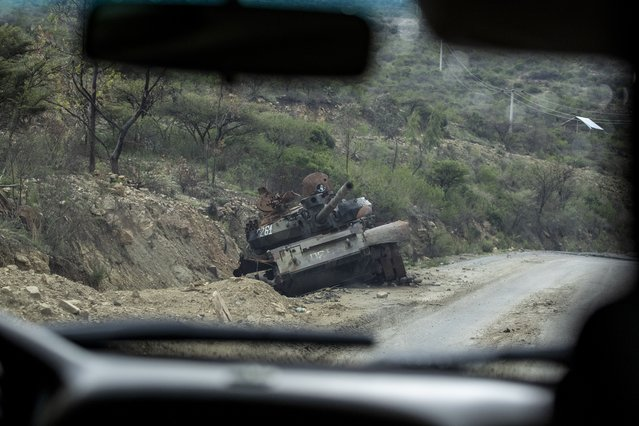 A destroyed tank sits by the side of a road leading to Abi Adi, in the Tigray region of northern Ethiopia, on Tuesday, May 11, 2021. The Tigray People's Liberation Front was on top of a coalition that ruled Ethiopia for nearly three decades. That changed in 2018, when Prime Minister Abiy Ahmed rose to power as a reformist. Abiy alienated the TPLF with efforts to make peace with its archenemy, Eritrea, and rid the federal government of corruption. (Photo by Ben Curtis/AP Photo)