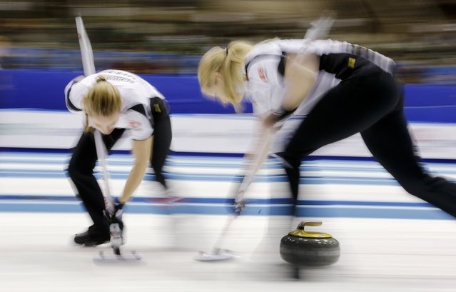 Switzerland's lead Nicole Schwaegli (L) and second Marisa Winkelhausen sweep during their curling round robin game against Japan at the World Women's Curling Championships in Sapporo March 14, 2015. (Photo by Thomas Peter/Reuters)