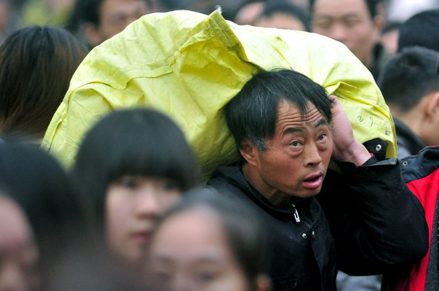 A man carries a bag on his back in Guangzhou, Guangdong province, January 26, 2016. According to traffic police, over 2.9 billion trips will be made around China during the 40-day Spring Festival travel rush, which started on January 24. (Photo by Reuters/Stringer)
