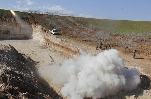 Rebel fighters fire Grad rockets toward forces of Syria's President Bashar al-Assad stationed in al-Suqaylabiyah district, from the orchards north of Kfar Zeita village in the northern countryside of Hama January 29, 2015. (Photo by Mohamad Bayoush/Reuters)