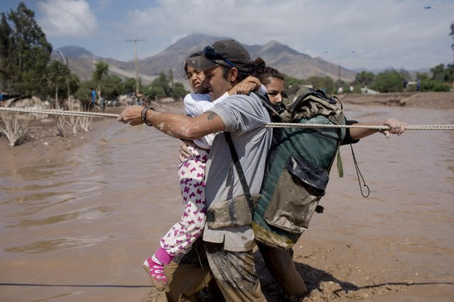 A family holds on a rope as they cross a flooded street in Copiapo, Chile, Thursday, March 26, 2015. (Photo by Pablo Sanhueza/AP Photo)