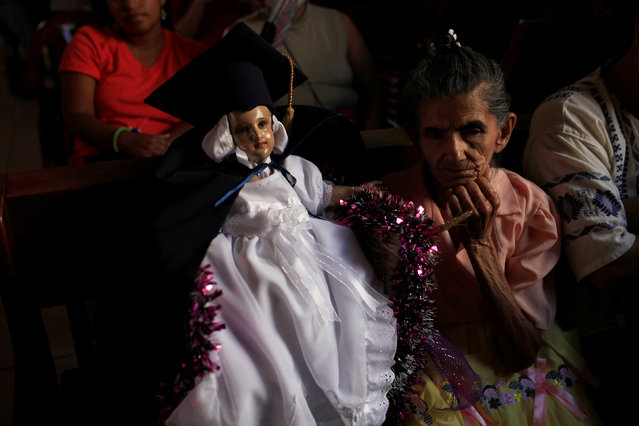 A Catholic faithful holds a figurine of baby Jesus as she waits for a religious procession on Holy Innocents Day in Antiguo Cuscatlan, El Salvador, December 28, 2016. (Photo by Jose Cabezas/Reuters)